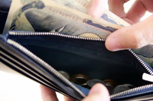 長財布からお金を取り出す