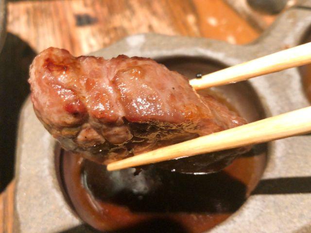 タレをつけた肉を食べる