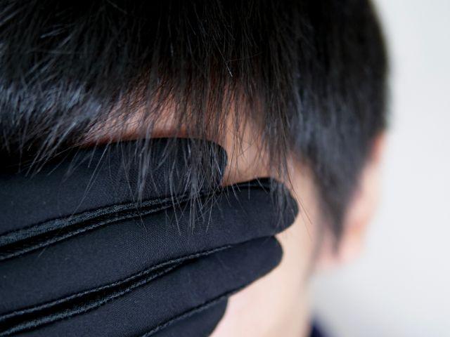 手袋で顔の汗を拭う