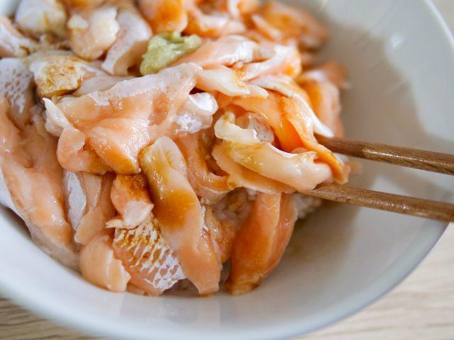 トロサーモン丼をお箸ですくう