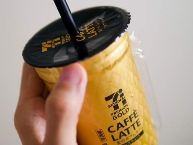 ストローをさしたカフェラテを手に持つ