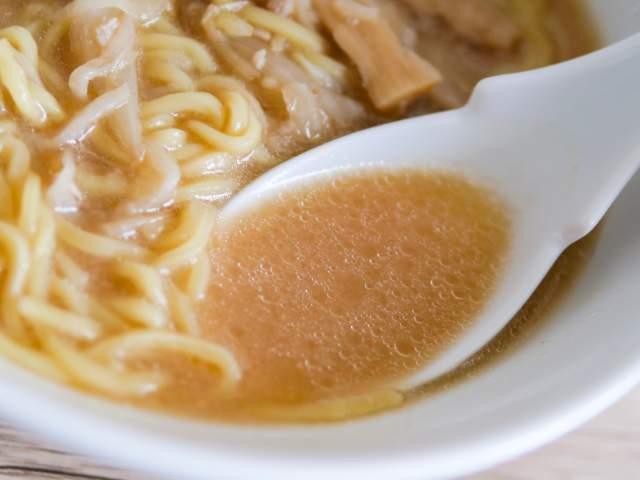 味噌ラーメンのスープをすくう