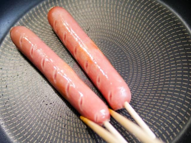 フライパンで串つきフランクフルトを焼く